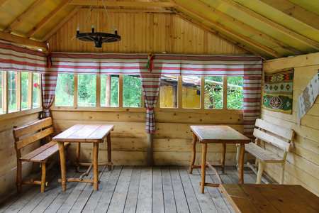 Old Ukrainian style pavilion with wooden tables and benches