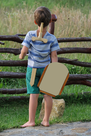 Boy with wooden sword and shield stands before stone Stock Photo