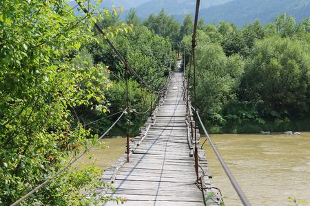 Suspended wooden bridge across Schodnica river in Carpathians, Ukraine Stock Photo