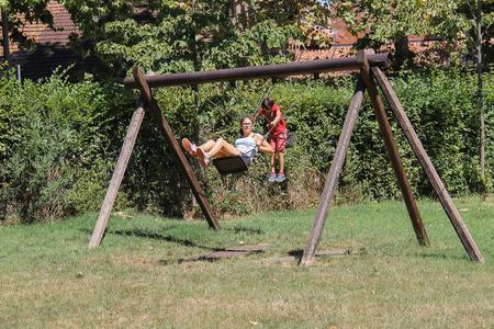 chain swing ride: Grazzano Visconti, Italy - August 07, 2016: Children ride on wooden swing