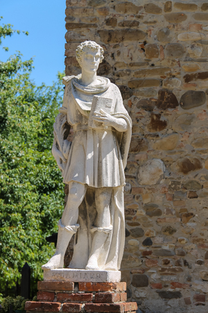 head stones: Marble statue of St. Damian at the entrance to the parish of Cosmas and Domian, Grazzano Visconti, Italy Stock Photo