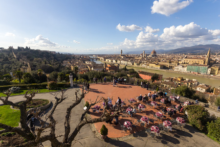 Tourists enjoying a panoramic view from Piazzale Michelangelo Square over Old Town Florence with Ponte Vecchio Bridge across Arno River beautiful architectures under sunset sky in Firenze, Italy