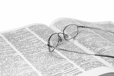 photo story: closeup of opened book and glasses isolated on white.monochrome image Stock Photo