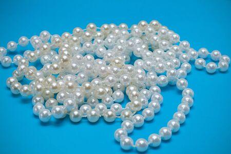una collana di perle su sfondo blu Archivio Fotografico - 4722487