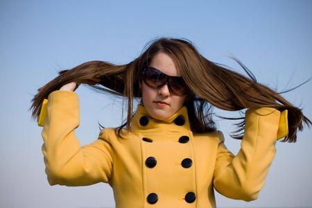 beautiful girl with sunglass wearing winter yellow coat over sky photo