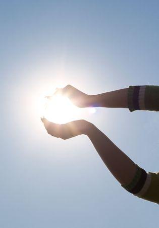 Woman's hands holding sun over blue sky Stockfoto