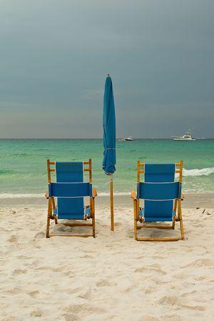 Beach lounge chairs over cloudy sky. Destin, Florida, USA photo