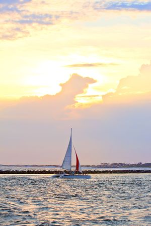 Sailboat at the ocean in sunset time photo