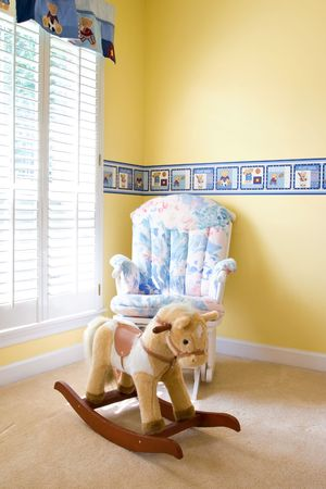 Babys bedroom with horse toy and armchair
