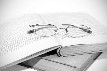 monochrome image of book and glasses photo