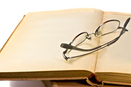 vintage book and glasses isolated on white photo