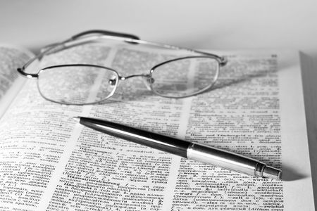 monochrome image of open dictionary with a pair of glasses and pen laying on top Stock Photo - 5932891