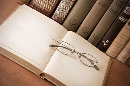 Book and glasses in the library. Vintage style photo