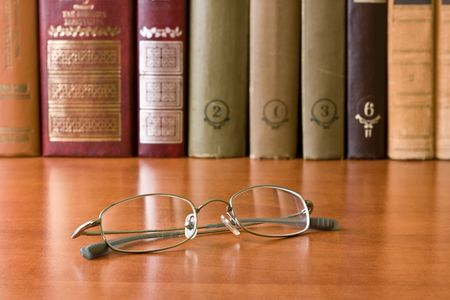 glasses with old hardcover books on bookshelf photo