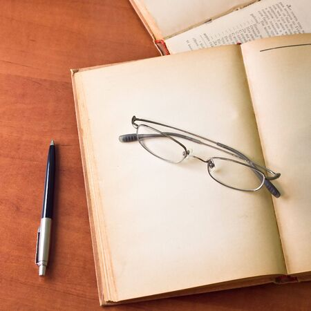 old books with reading glasses and pen on desk photo