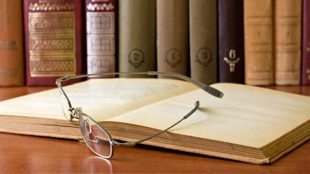 glasses in front of an old books in library photo