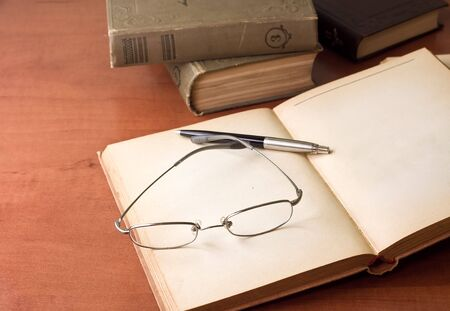 closeup of opened book, pen and glasses photo