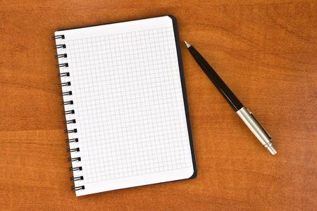 notitieboekje met pen op bruine houten achtergrond Stockfoto