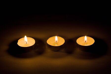 Three burning candles on black photo