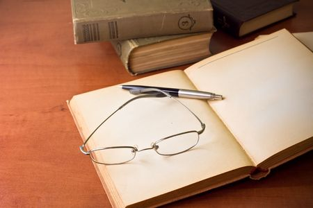 library desk with books, glasses and pen photo