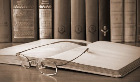 book and glasses in library. Vintage style photo