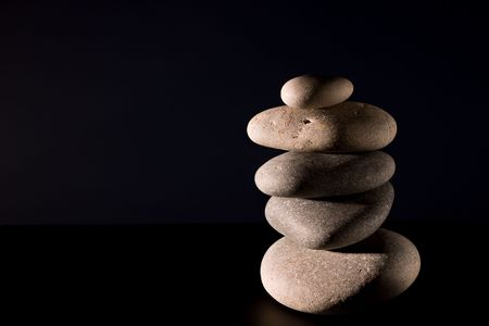 five stones in zen balance over black background photo