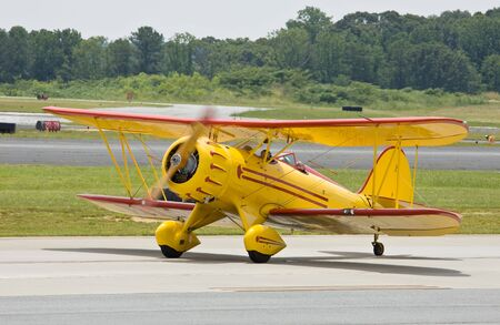 biplane: yellow vintage airplane landing Stock Photo
