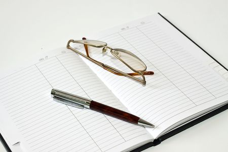 datebook: Datebook, pen and glasses on white background