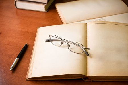 untidiness: library desk with books, glasses and pen