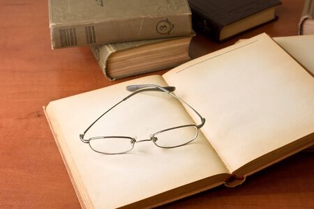 Pile of old books with reading glasses on desk photo