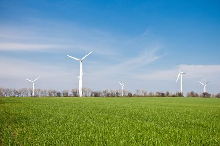 Panorama view of wind energy turbines with green field, blue sky and clouds Stock Photo - 6854276
