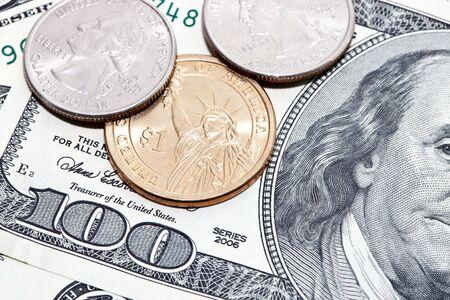 coins over hundred dollar bills background Stock Photo
