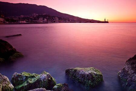 Rocky beach sunrise over sea photo