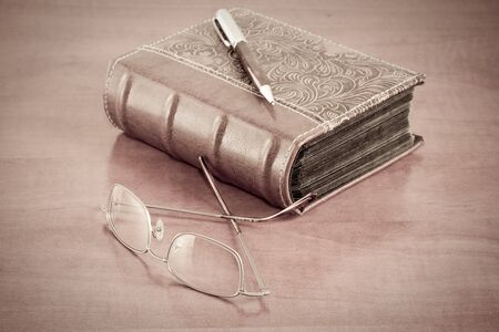 old book with reading glasses and pen on desk photo