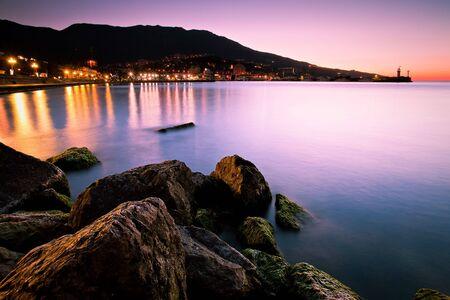 zee landschap tijdens zonsopgang met stadslichten. Zwarte Zee, Jalta, Oekraïne