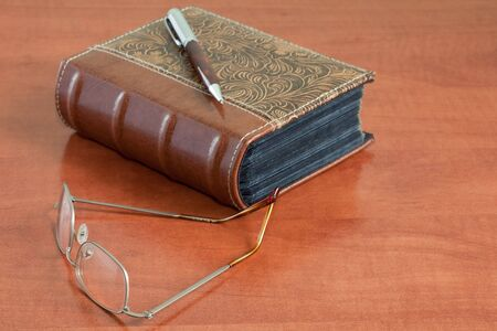 library desk with old book, glasses and pen photo