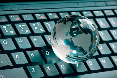 information international: small glass globe on a laptop keyboard