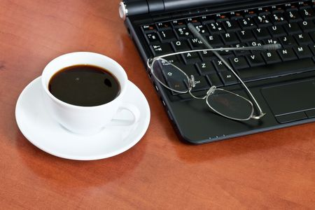 cup of coffee with a laptop and glasses close up Stock Photo - 7235299
