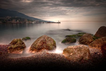 dramatic seascape with rocky beach and lighthouse photo