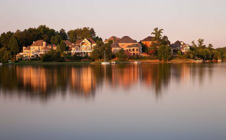 Beautiful scene of houses by the lake surrounded by forests  at sunset time