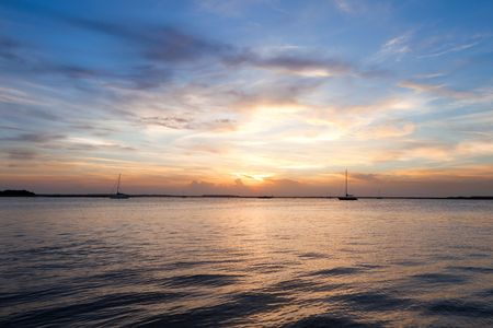 Sailing boat silhouette over sunset sky. Fernandina beach, Florida, USA