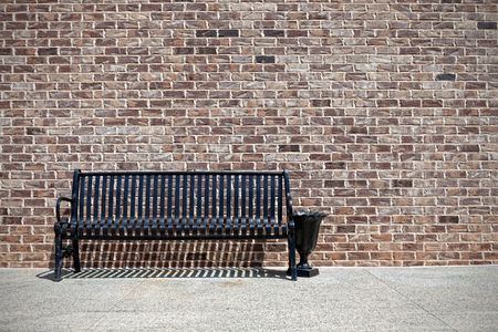 outdoor pursuit: Metal bench against a brick wall Stock Photo