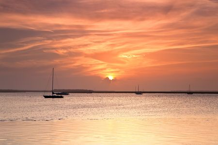 Sailing boat silhouette and red sunset over the ocean