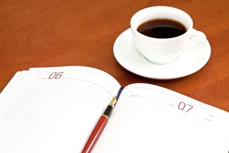 Coffee cup, notebook and pen on the wooden table Stock Photo - 7939764