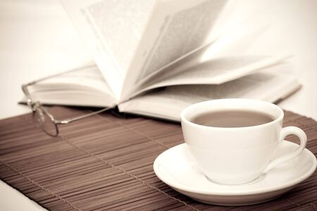 retro image of white cup of coffee and book with glasses on table photo