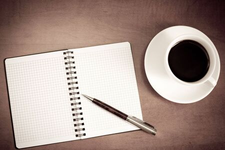 Coffee cup, spiral notebook and pen on the wooden table Stock Photo - 7939920