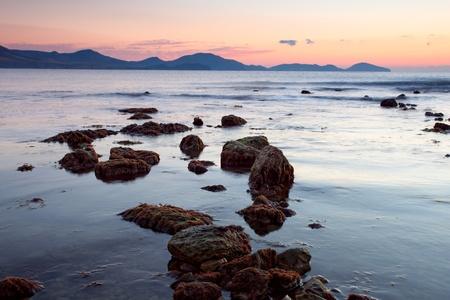 colorful sunrise on the rocky coast of sea photo