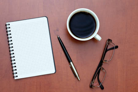 Pen, white spiral notebook and glasses with cup of coffee on the desk Stock Photo - 8571993