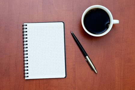 Pen on a white spiral notebook with cup of coffee on the desk Stock Photo - 8600025