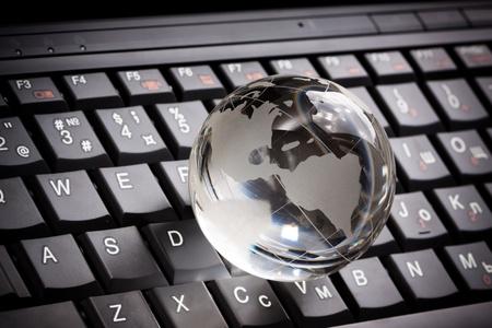 Crystal globe op laptop toetsenbord Stockfoto